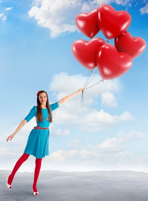 Woman holding a group of heart shaped balloons